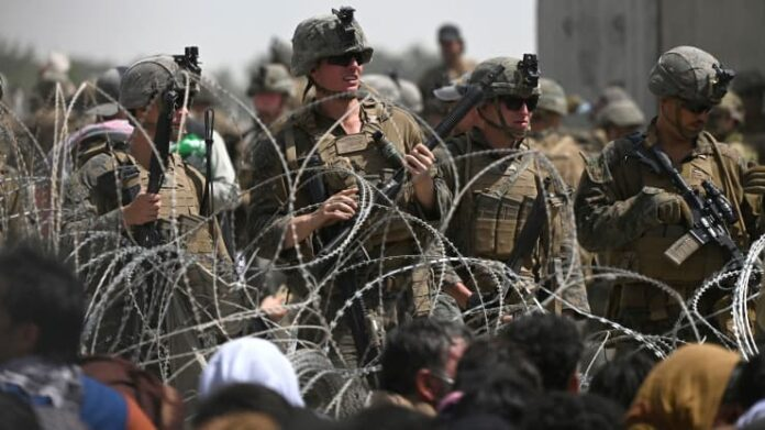 US soldiers stand guard behind barbed wire as Afghans
